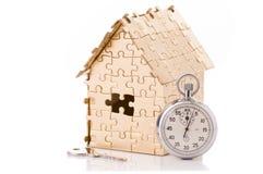 Huis van gouden kleurenraadsels met een chronometer Stock Fotografie