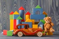 Huis van houten blokken, dichtbij een stuk speelgoed dat en houten wordt gemaakt te assembleren Stock Afbeelding