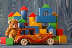 Huis van houten blokken, dichtbij een stuk speelgoed dat en houten wordt gemaakt te assembleren Stock Foto's