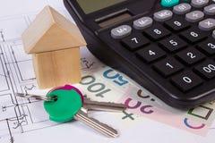 Huis van houten blokken en poetsmiddelgeld met calculator op bouwtekening, de bouw huisconcept stock foto