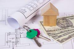 Huis van houten blokken, sleutels en muntendollar op bouwtekening, de bouw huisconcept Royalty-vrije Stock Foto