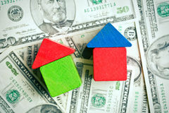 Huis van houten stuk speelgoed blokken op dollarachtergrond die wordt gemaakt Stock Foto