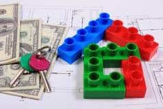 Huis van kleurrijke bouwstenen, sleutels en bankbiljetten op tekening Stock Foto's