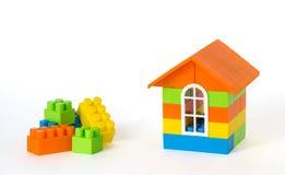 Huis van plastic bakstenen en sommige blokken opzij wordt gemaakt dat Geïsoleerdj op witte achtergrond Stock Foto