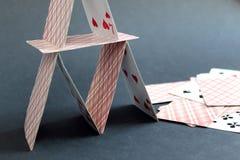 Huis van speelkaarten op een zwarte achtergrond wordt gebouwd die royalty-vrije stock foto