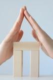 Huis van stuk speelgoed blokken met handen als dak wordt gemaakt dat Stock Foto