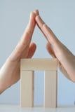 Huis van stuk speelgoed blokken met handen als dak wordt gemaakt dat Stock Fotografie