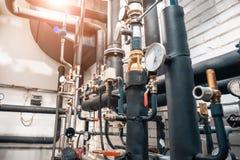 Huis verwarmingssysteem in ketelruim met vele staalpijpen, manometers en metaalbuizen stock foto's