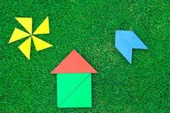 Huis, vliegtuigen en zon van tangram cijfers aangaande natuurlijk gras wordt gemaakt dat Royalty-vrije Stock Foto