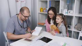 Huisarts De arts van mannelijke kinderen onderzoekt een geduldig meisje stock videobeelden