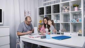 Huisarts Moeder en weinig dochter in de spreekkamer voor onderzoek stock footage