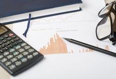 Huisbesparingen, begrotingsconcept Grafiek, blocnote, calculator en glazen op houten bureaulijst Royalty-vrije Stock Foto's