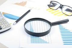 Huisbesparingen, begrotingsconcept Grafiek, glazen, pen, calculator en vergrootglas op houten bureaulijst Stock Foto