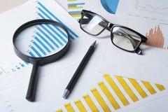 Huisbesparingen, begrotingsconcept Grafiek, glazen, pen en vergrootglas op houten bureaulijst Stock Foto's