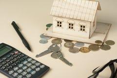 Huisbesparingen, begrotingsconcept Modelhuis, blocnote, pen, calculator en muntstukken op houten bureaulijst Stock Foto's
