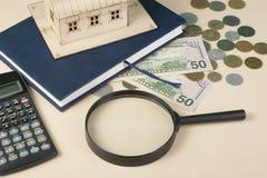 Huisbesparingen, begrotingsconcept Modelhuis, blocnote, pen, calculator en muntstukken op houten bureaulijst Stock Fotografie