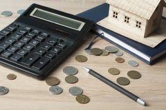 Huisbesparingen, begrotingsconcept Modelhuis, blocnote, pen, calculator en muntstukken op houten bureaulijst Stock Foto