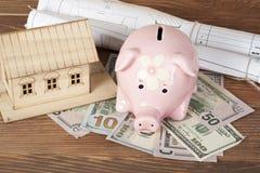 Huisbesparingen, begrotingsconcept Modelhuis, spaarvarken, geld op houten bureaulijst Stock Afbeelding