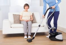 Huisbewaarder schoonmakende vloer terwijl hogere vrouwenzitting op bank Stock Fotografie