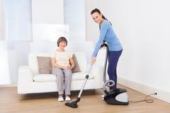 Huisbewaarder schoonmakende vloer terwijl hogere vrouwenzitting op bank Stock Foto