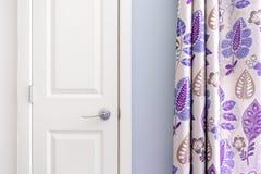 Huisbinnenland die koloniale kastdeur met purper gordijndecor en lichtblauwe geschilderde muur tonen stock afbeelding