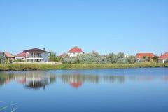 Huisbouw met vele huizen en plattelandshuisjes op de meerbank met mooie mening royalty-vrije stock fotografie
