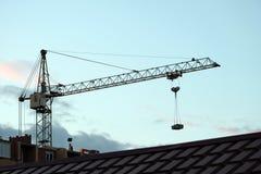 Huisbouw Pijl van een torenkraan met een lading tegen de achtergrond van de avondhemel Betegeld dak in de voorgrond stock foto's