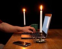 Huisbureau met Laptop door Kaarslicht wordt verlicht dat Royalty-vrije Stock Foto's