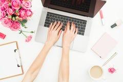 Huisbureau Vrouwenwerkruimte met vrouwelijke handen, laptop, roze rozenboeket, toebehoren, agenda op wit Hoogste mening Vlak leg stock afbeelding