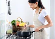 Huischef-kok het koken in de keuken stock afbeeldingen