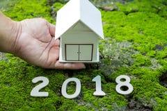 Huisconcepten 2018, Nummer 2018 met huismodel op hand met gr. Stock Afbeelding