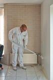 Huisdecorateur die een muur met een rol schilderen stock foto