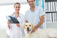 Huisdiereneigenaar en dierenarts met Röntgenstraal van hond Royalty-vrije Stock Afbeeldingen