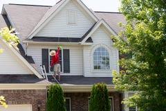 Huiseigenaar die de buitenkant van zijn huis wassen stock afbeeldingen