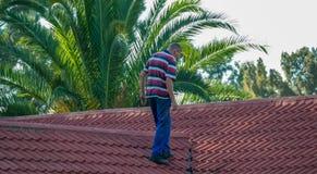 Huiseigenaar die het dak van zijn bezit bevestigen royalty-vrije stock afbeeldingen