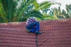 Huiseigenaar die het dak van zijn bezit bevestigen stock fotografie