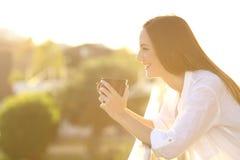 Huiseigenaar het ontspannen het drinken koffie in een balkon royalty-vrije stock fotografie