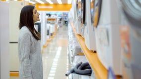 Huishoudapparatenopslag Een jonge vrouw kiest een wasmachine stock foto's