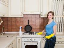 Huishoudelijk werk en huishoudenconcept - gelukkige jonge vrouw met bott royalty-vrije stock fotografie