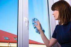Huishoudelijk werkconcept - vrouwen schoonmakend venster met vod thuis Royalty-vrije Stock Fotografie