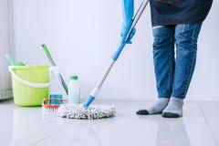 Huishouden en het schoonmaken concept, Gelukkige jonge vrouw in blauwe oneffenheid stock foto's