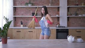 Huishoudenkarweien, vrolijk huisvrouwenmeisje die rond en in bezemsteel voor de gek houden tijdens Huis het schoonmaken dansen stock footage