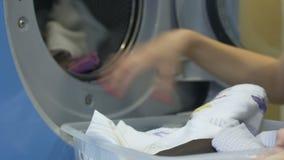 Huishoudenvrouw die zorgvuldig vuile kleren van mand laden aan wasmachine stock video