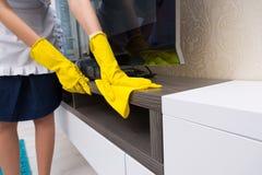 Huishoudster die en een TV-kabinet schoonmaken bestrooien royalty-vrije stock afbeeldingen