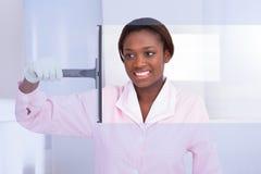 Huishoudster schoonmakend glas in hotel Stock Afbeelding