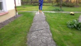 Huishoudstermens die concrete weg wassen dichtbij zijn huis stock video