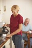 Huishulp die Kop thee met Hoger Mannetje in Keuken delen stock fotografie