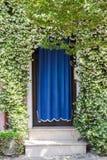 Huisingang met bloeiende installaties wordt behandeld die royalty-vrije stock foto's