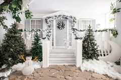 Huisingang voor vakantie wordt verfraaid die De decoratie van Kerstmis slinger van sparrentakken en lichten op het traliewerk Royalty-vrije Stock Fotografie