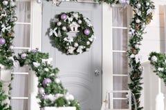 Huisingang voor vakantie wordt verfraaid die De decoratie van Kerstmis slinger van sparrentakken en lichten op het traliewerk Stock Foto's